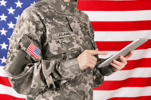 Veteran looking at iPad for education news witha flag in the background