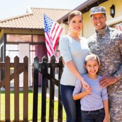 Military Family Standing In Front of New Home