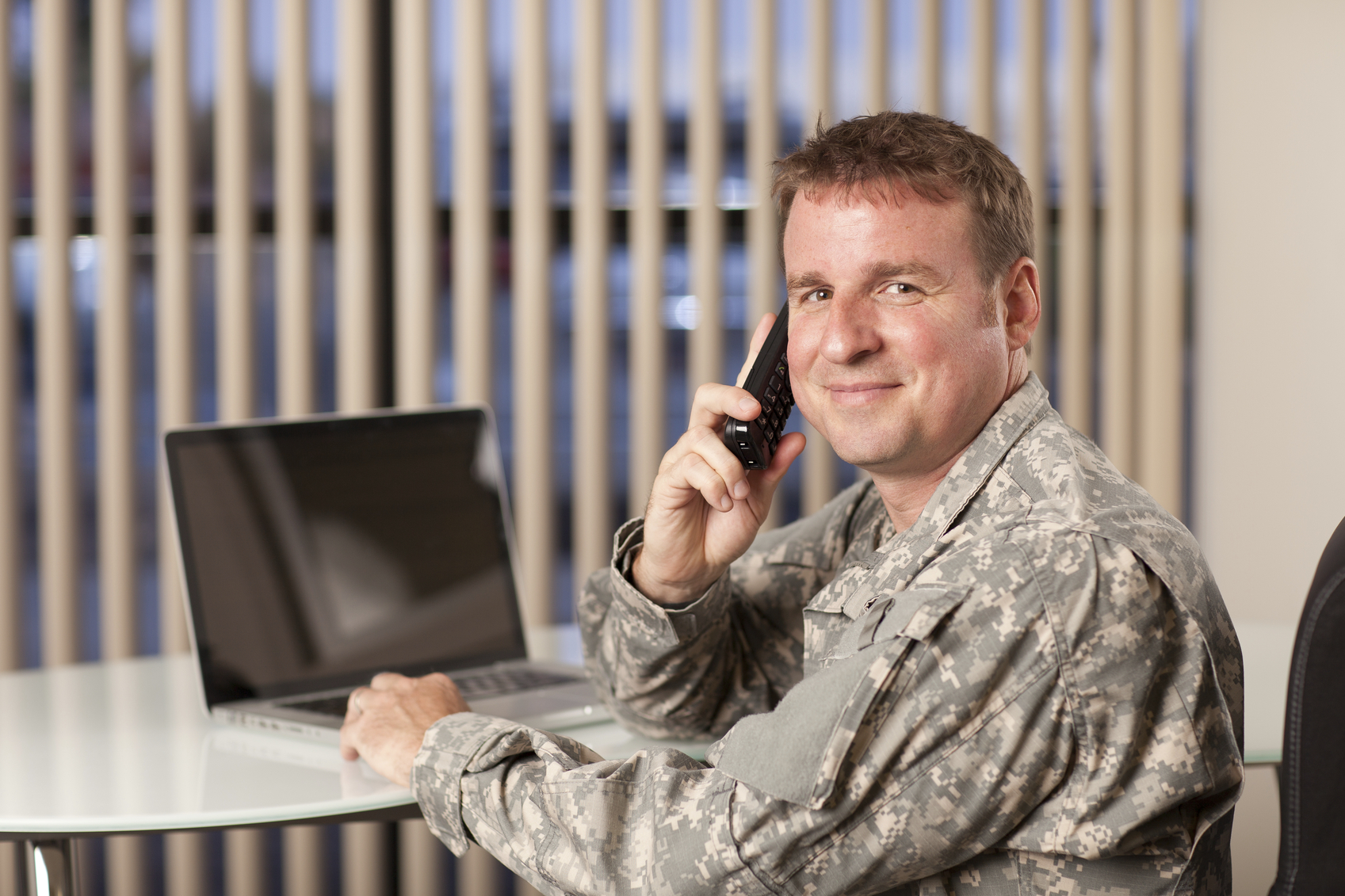 smiling soldier on the phone sitting a a desk