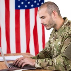Soldier using a laptop to code at desk