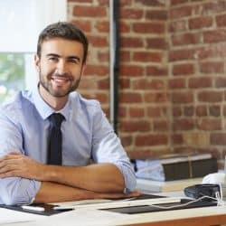 man sitting at a desk at work smiling witha rms folded in work casual clothes