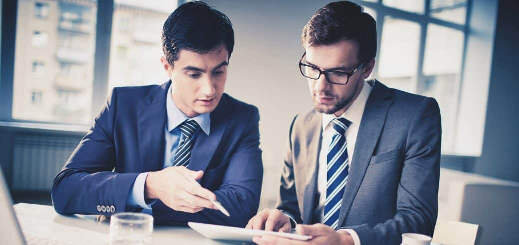 Two young men reviewing business documents