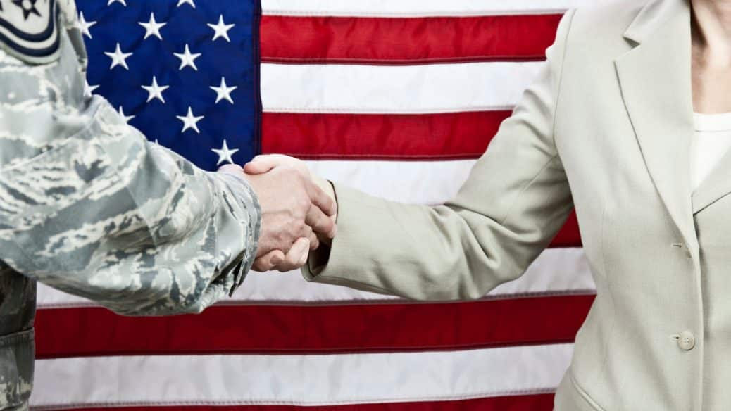 businessman shaking hands with veteran with U.S. flag behind them