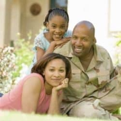 Military Spouse, husband in fatigues and daughter pose casually in frontyard