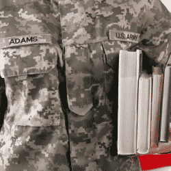 Veteran in uniform holding books with a U.S. flag behind him