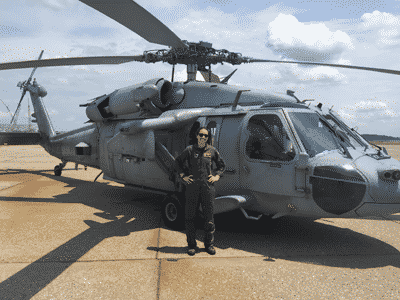 Rebecca Bennett standing next to army helicopter