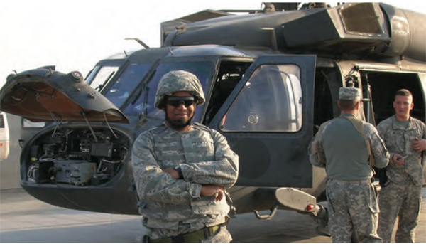Lt. Colonel Hooks poses in uniform in front of Helicopter
