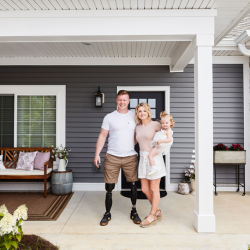 Disabled veteran and family stand outside their new home