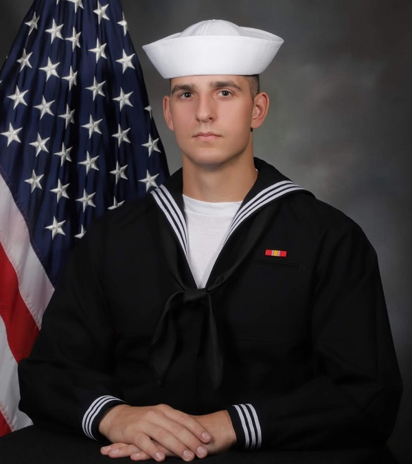 Kade Stepan sits in front of U.S. Flag in his Navy uniform