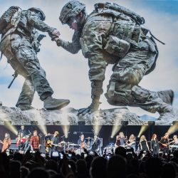 VetsAid concert performers and attendees with a big screenin the background showing one soldier helping another up a hill