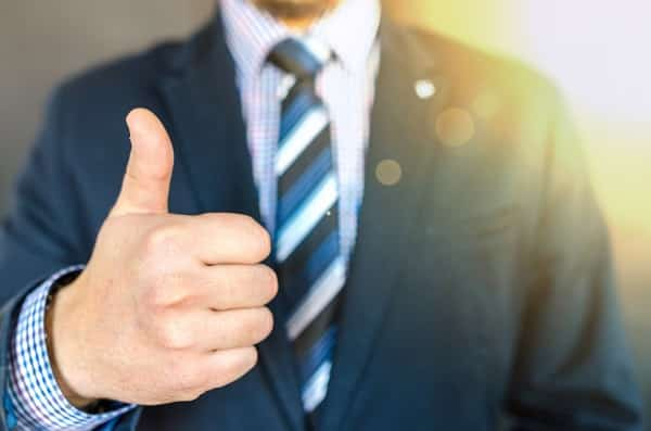 man in a suit giving a thumbs up signal