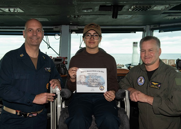 U.S. Navy Aviation Structural Mechanic Airman Lesley Carrasco, from Anaheim, California, poses for a photograph as the Sailor of the Day with Capt. Randy Peck, right, commanding officer of the aircraft carrier USS John C. Stennis (CVN 74), and Command Master Chief Marc Puco in the Atlantic Ocean, Nov. 8, 2019. The John C. Stennis is underway conducting routine operations in support of Commander, Naval Air Force Atlantic