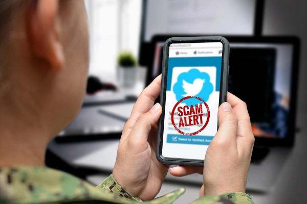 man in military uniform holding a smartphone with a scam alert image on it