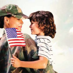 woman veteran holding child who has a U.S. Flag in his hand
