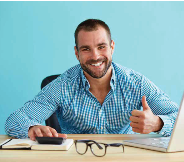 military veteran sitting at desk in civilian clothes giving a thumbs up
