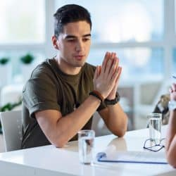Young depressed military man talking about emotional problems with psychotherapist at doctor's office