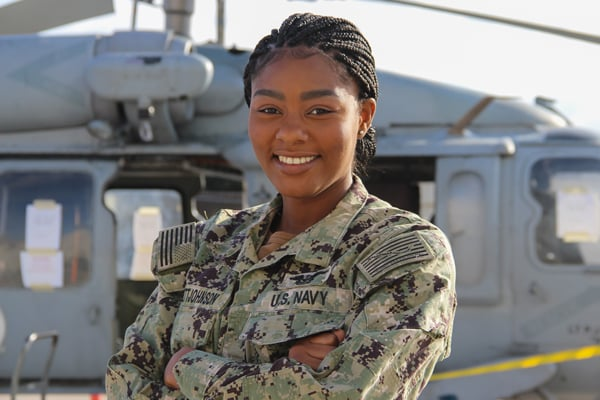 US Navy sailor standing in front of helicopter