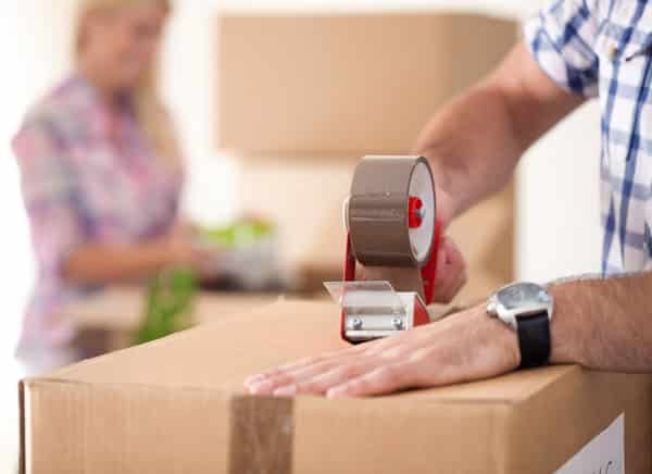 Close up of male hand packing property in cardboard box with spouse in the background