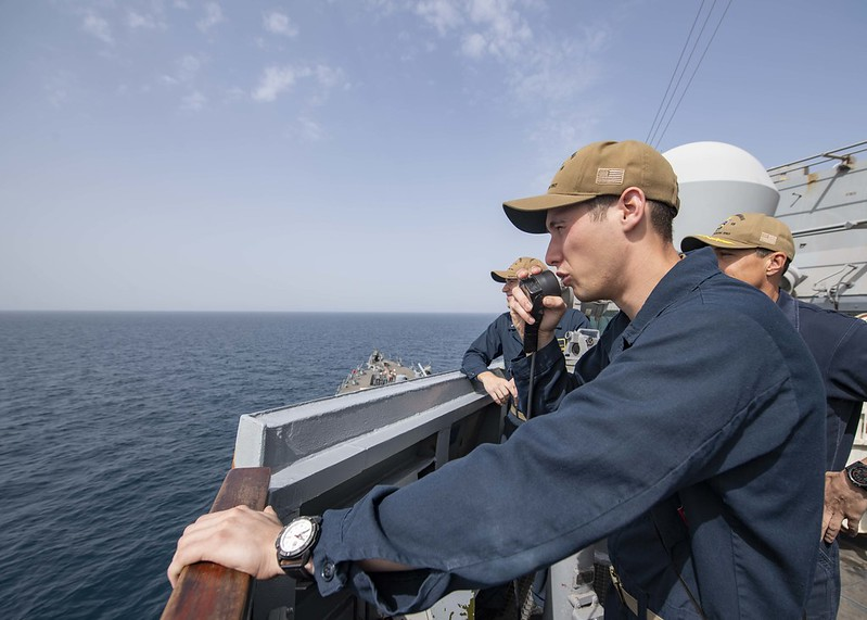 Sailor speaks into sound-powered telephone during ship handling drills
