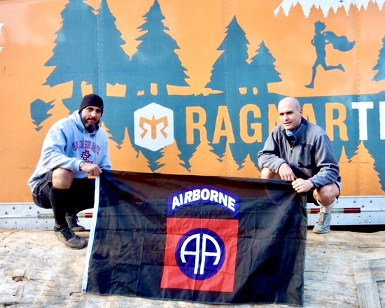 Heath Hansen and buddy kneeling on ground holding an Airborne flag