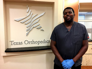 Navy Veteran Kendrick Cowans is pictured at work next to the Texas Orthopedics office sign