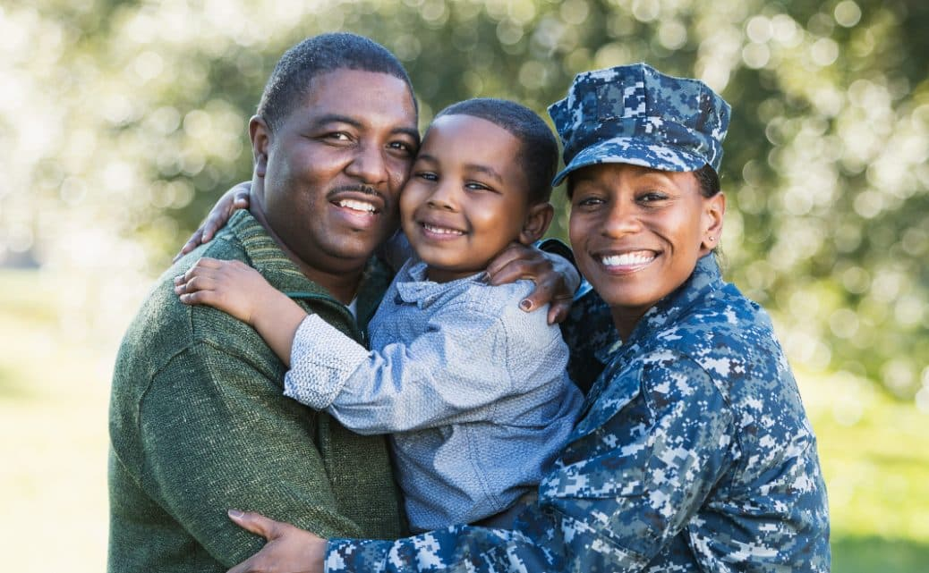 Happy Military Family wife dreeses in fatigues holding child in arms with husband outside setting