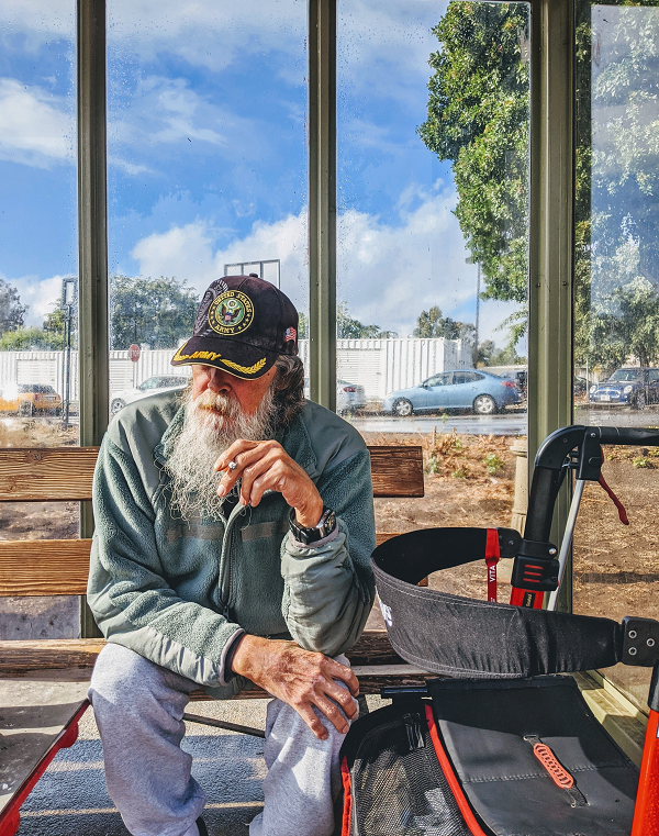 homelesss veteran sits on bench outside looking solemn