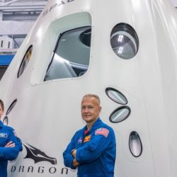 Colonels Bob Behnken and Doug Hurley crossing their arms in front of the Dragon spacecraft