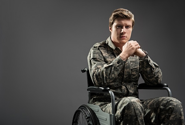 A military veteran sitting in a wheelchair in his uniform, looking at the camera