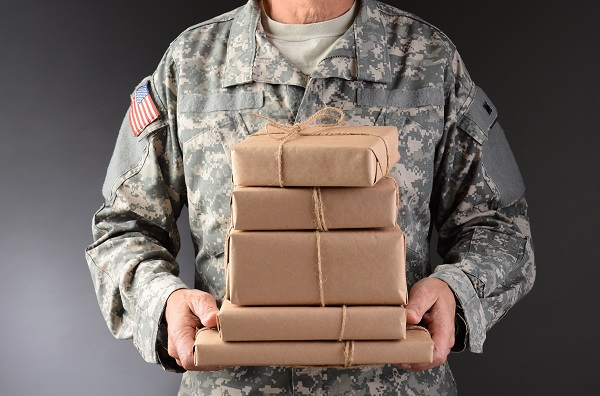 A man in a military uniform holding a stack of packages
