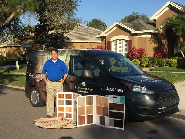 Mark McMurray pictured outside in front of his floor coverings vehicle with large samples displayed