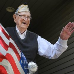 veteran witha huge grin in a shriners hat waving with U.S. flag in the background