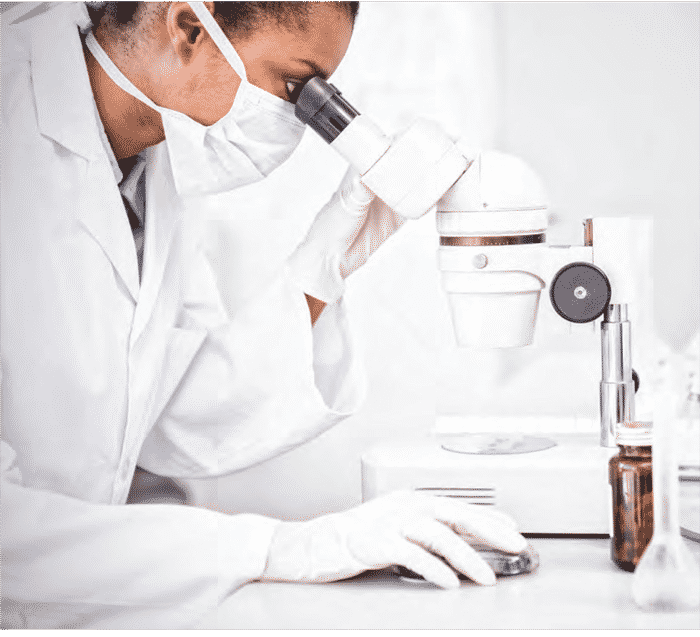 Woman working in a laboratory wearing face mask and white lab coat looking in to a microscope