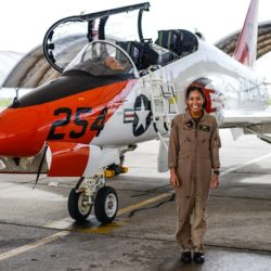 Lt. Madeline Swegle standing in front of NAVY aircraft in uniform smiling