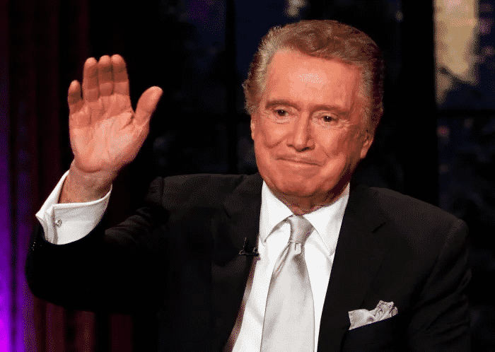 Regis Philbin sitting waving hand in air to audience smiling