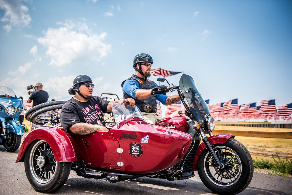 two military veterans riding on a side car motorcycl with others following behind during the event