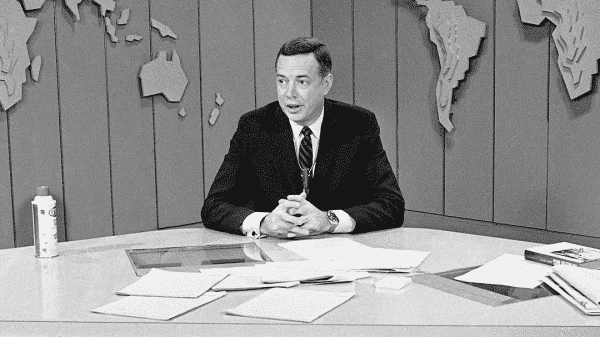 hugh downs seated in tv anchor chair while doing the nightly news in the 60's