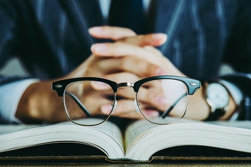 A pair of glasses sitting on a book in front of a man in a suit with his hands folded