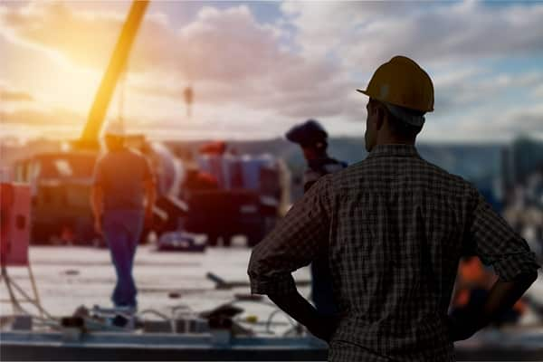 A man looking out on a construction site