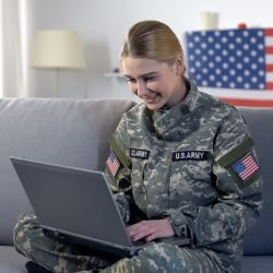 A woman in a military outfit looking at her laptop