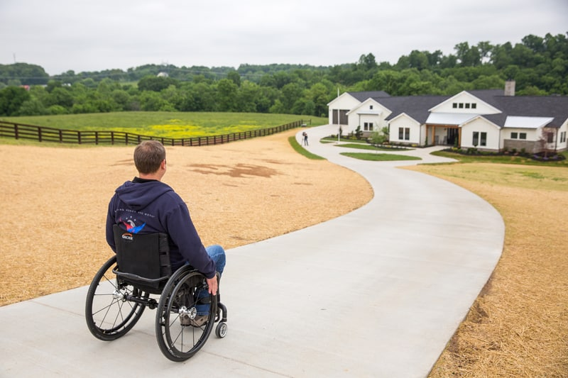 Gary Linfoot coming down the sidewalk in wheelchair with new large home in the distance on a large piece of grassy property