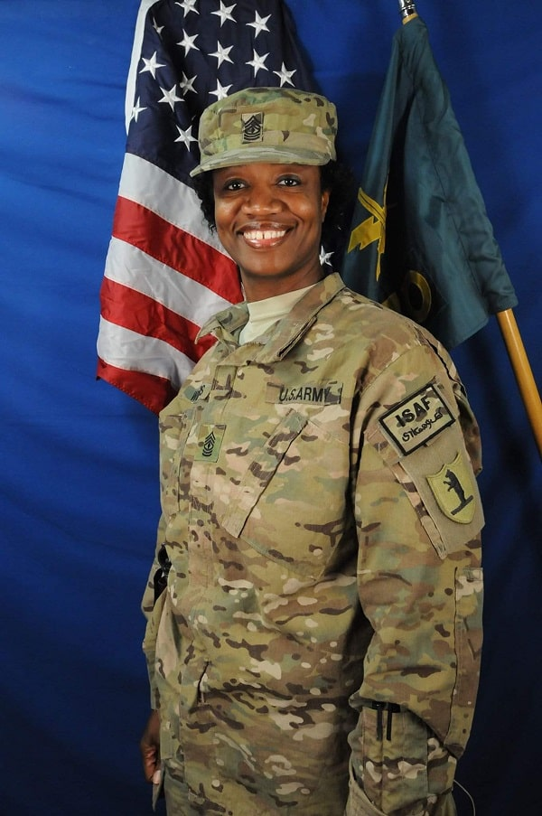 Mary Lester Military Veteran in Uniform smiling with US flag in the background