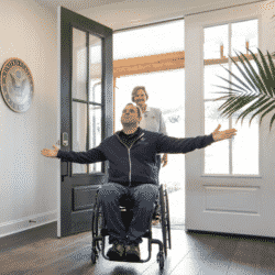 Wounded Army Chief Gary Linfoot in wheelchair in doorway of new home arms spread wide palms open and looking up thankfully with wife behind him