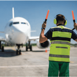 airport employer holding guiding sticks for airplane to taxi in