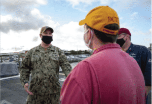 William Merchen wearing a mask an fatigues visiting the USS Cole