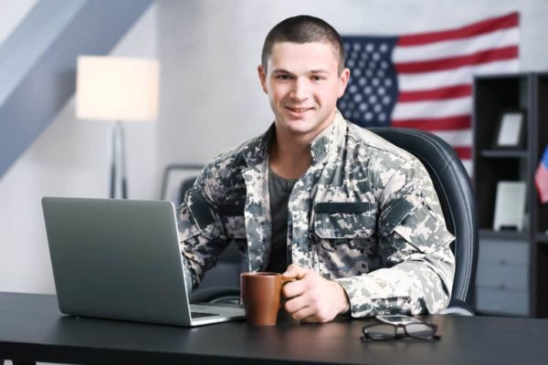 Soldier working on a laptop with US Flag in the background