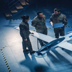 Three active duty personnel having a discussion in front of a model airlplane