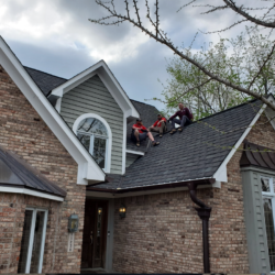 Three contractors from Hoosier Contractors sit on top of their newly completed roofing project