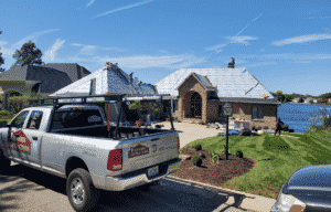 Contractors work on a full roof replacement for a home in the suburbs of Indianapolis