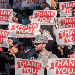 group of military supporters gathered holding signs that say thank you